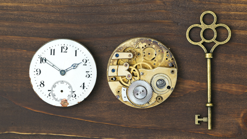 Vintage ornate key, clock face and watch mechanism, escape room, time concept