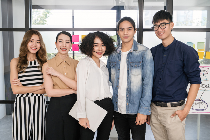 Portrait of Asian creative business team. Hipster Creative Startup Young business people in modern office.