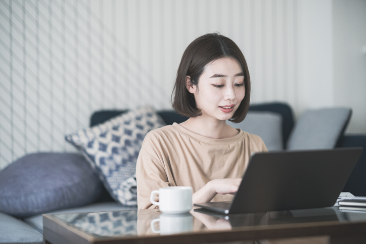 Asian young woman working remotely with laptop in room at home