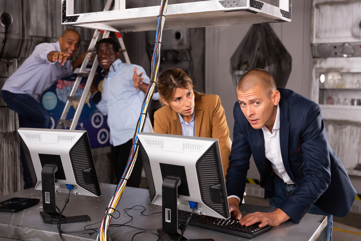 Young adult male and female colleagues trying to solve conundrum using computer to get out of escape room during corporate event