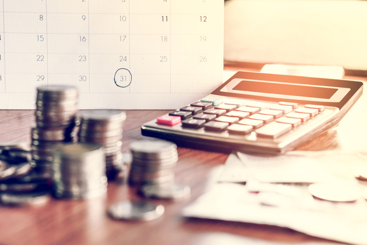 debt collection and tax season concept with deadline calendar remind note,coins,banks,calculator on table, background ,time to pay concept